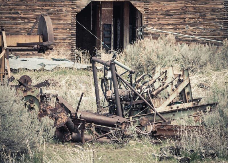 Vieilles machines par un élévateur à grains abandonné photo libre de droits