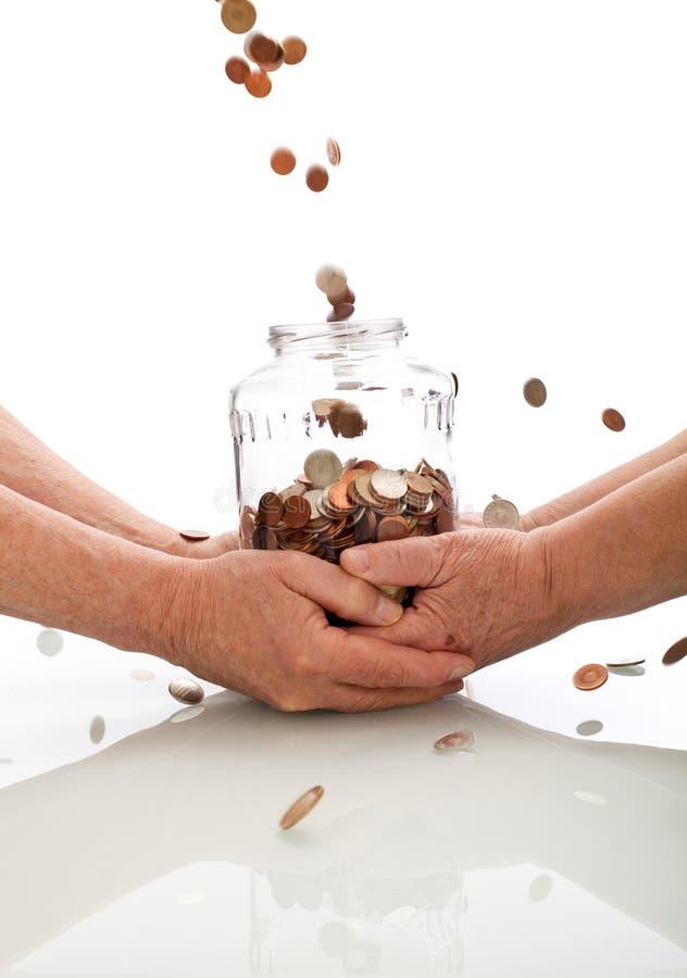 Vieilles mains retenant les pièces de monnaie en baisse attrapantes de choc image stock