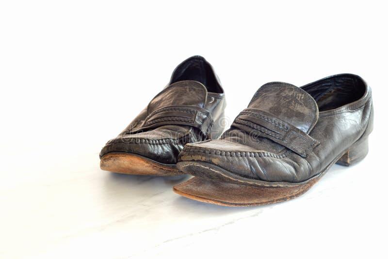 Vieilles paires des chaussures élégantes noires en cuir des hommes qui sont portées, très poussiéreux et sale et tombant en morce photos libres de droits