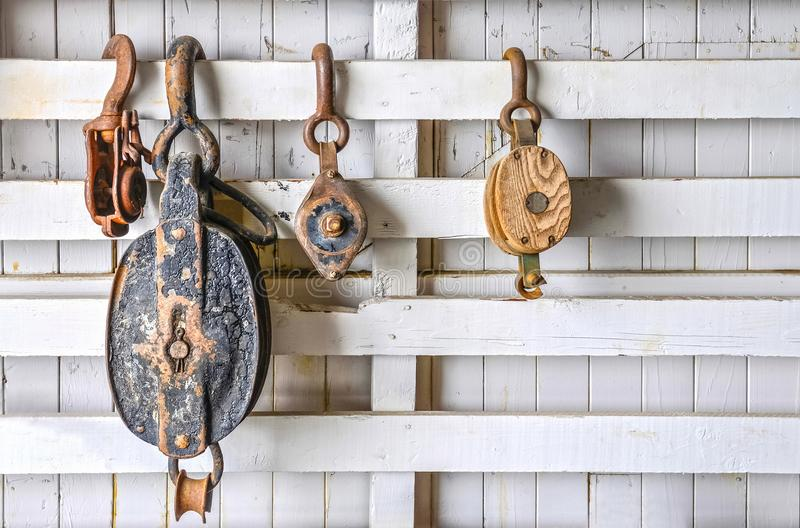 Vieilles poulies sur un mur en bois blanc images stock
