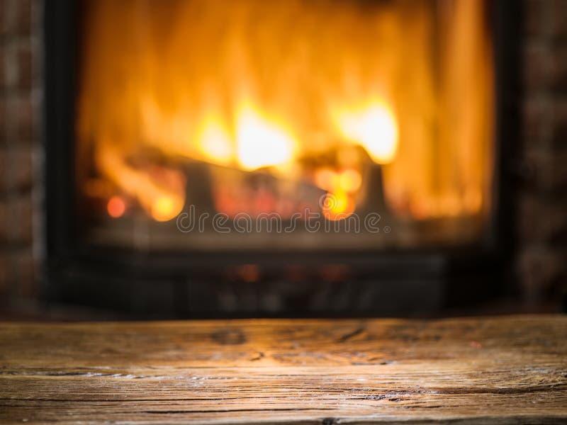 Vieilles table et cheminée en bois avec le feu chaud photographie stock