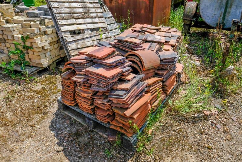 Vieilles tuiles de toit abandonnées d'argile se trouvant sur une palette dans une vieille cour photos stock