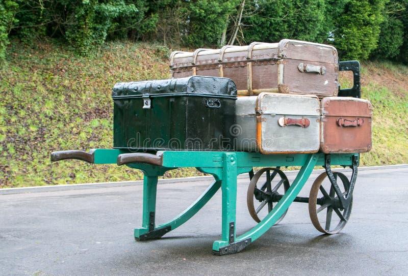 Vieilles valises battues sur une brouette à une gare ferroviaire photographie stock