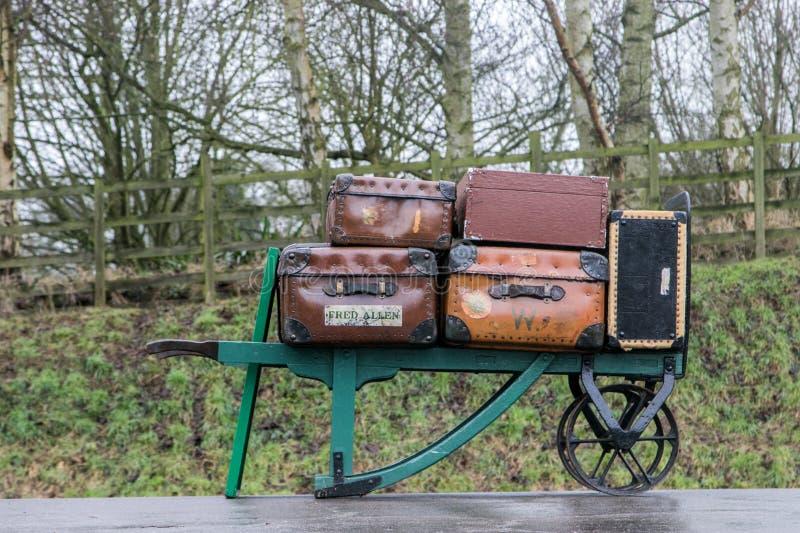 Vieilles valises battues sur une brouette à une gare ferroviaire photos libres de droits