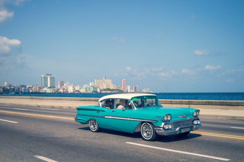 Vieilles voitures classiques bleues sur le Malecon, la promenade iconique de bord de mer, à La Havane image libre de droits
