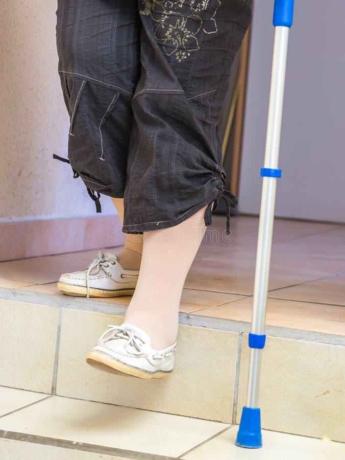 vieillissez la femme avec une béquille en bas des escaliers photo stock