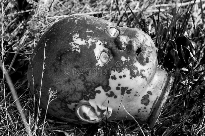 Vieja cabeza espeluznante de la muñeca Juguete asustadizo dañado abandonado quebrado en una descarga de basura foto de archivo