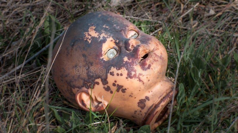 Vieja cabeza espeluznante de la muñeca Juguete asustadizo dañado abandonado quebrado en una descarga de basura fotos de archivo