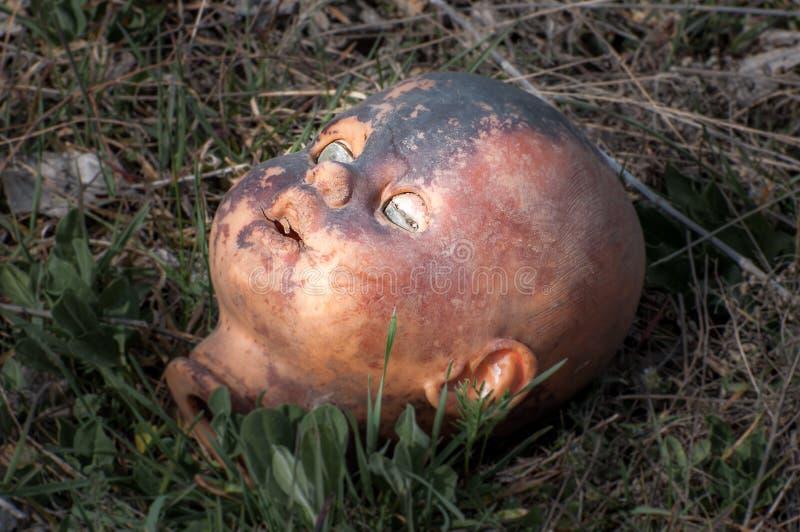 Vieja cabeza espeluznante de la muñeca Juguete asustadizo dañado abandonado quebrado en una descarga de basura foto de archivo libre de regalías