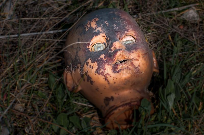 Vieja cabeza espeluznante de la muñeca Juguete asustadizo dañado abandonado quebrado en una descarga de basura imagenes de archivo