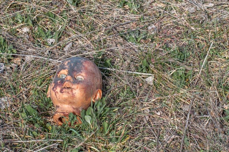 Vieja cabeza espeluznante de la muñeca Juguete asustadizo dañado abandonado quebrado en una descarga de basura imágenes de archivo libres de regalías
