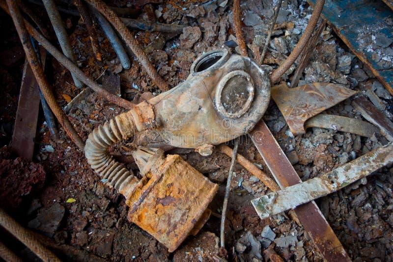 Vieja careta antigás soviética putrefacta con el filtro oxidado en el piso oxidado del metal de la nave con basura fotografía de archivo libre de regalías