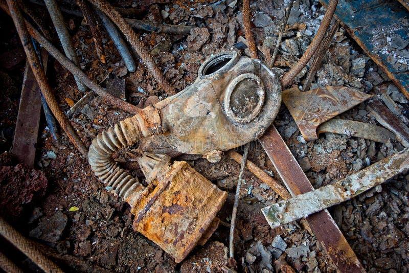 Vieja careta antigás soviética putrefacta con el filtro oxidado en el piso oxidado del metal de la nave con basura fotos de archivo libres de regalías