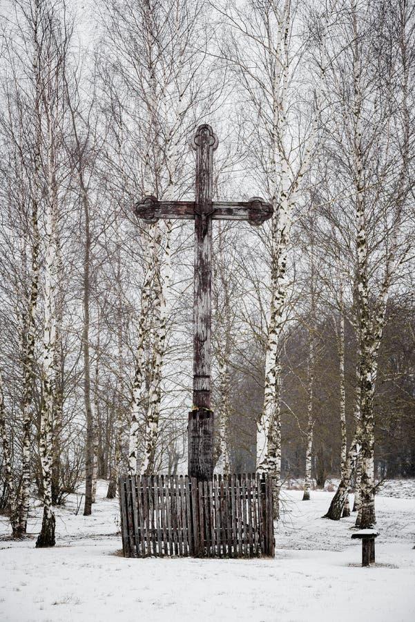 Vieja cruz de madera en un pequeño parque de abedules en invierno fotografía de archivo