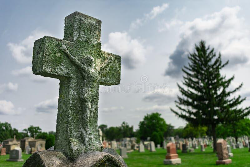 Vieja cruz encima de una piedra sepulcral en un cementerio imagenes de archivo