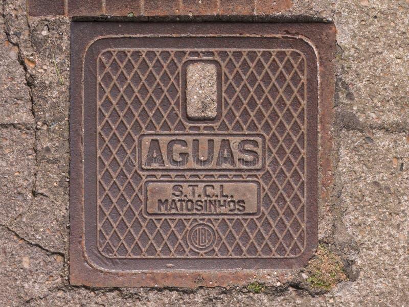 Vieja cubierta del dren del metal en Povoa de Varzim, Portugal con los AGUAS que ponen letras y el modelo de la marca de rayitas  fotografía de archivo