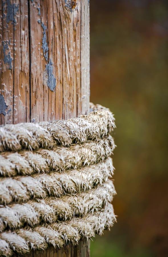 Vieja cuerda que amarra envuelta en un polo de madera mientras que sostiene el buque amarrado imagen de archivo