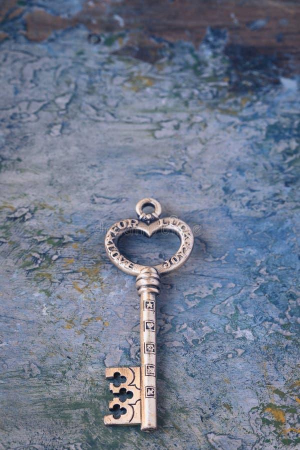 Vieja llave aislada en fondo concreto con símbolos del amor, alegría, amistad, suerte imagen de archivo libre de regalías