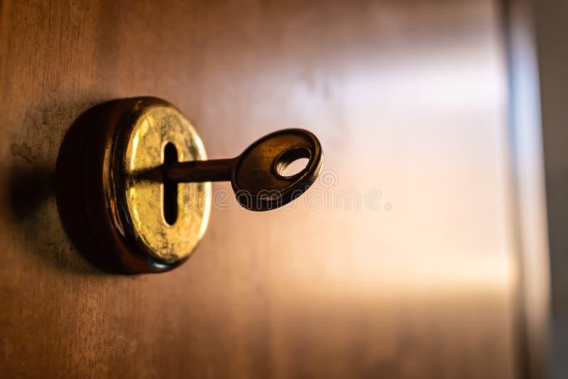 Vieja llave del metal dentro de la cerradura con el fondo borroso puerta de madera fotografía de archivo