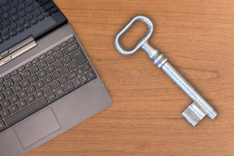 Vieja llave grande y ordenador portátil fotos de archivo