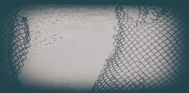 Vieja malla metálica quebrada contra la nieve Bandera del Web fotos de archivo