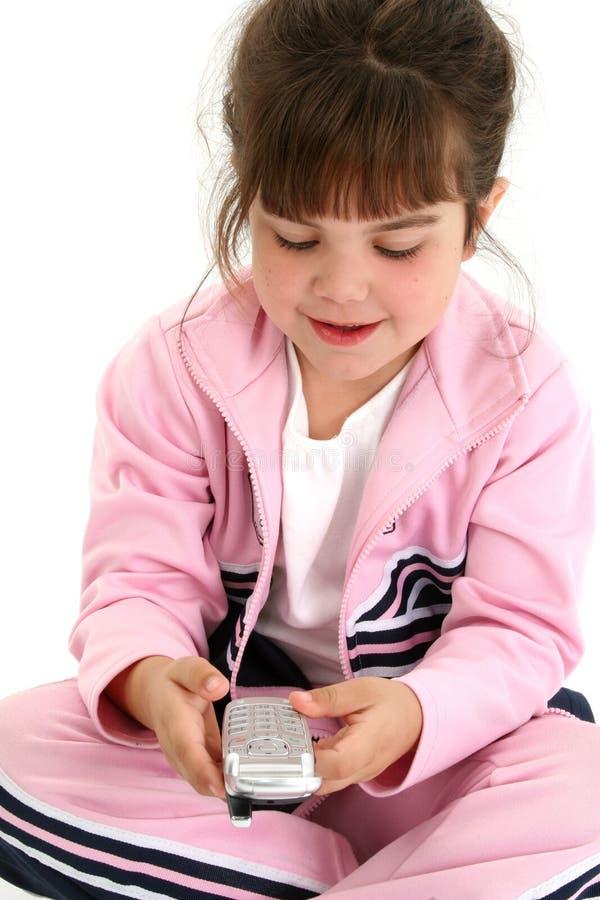 Vieja muchacha de cinco años hermosa en ropa rosada del entrenamiento con Cellph foto de archivo libre de regalías