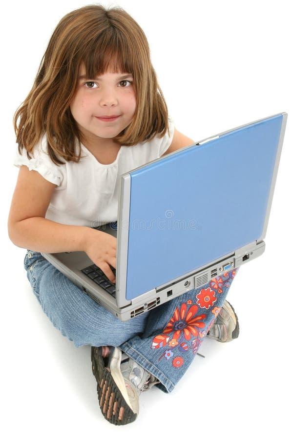 Vieja muchacha de cinco años hermosa que se sienta en suelo con la computadora portátil imagen de archivo