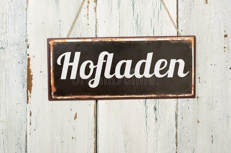 Vieja muestra delante de una pared de madera blanca - palabra alemana del metal para la tienda de la granja - Hofladen fotos de archivo