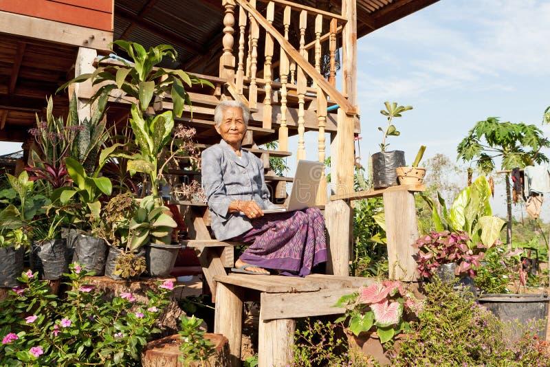 Vieja mujer asiática con la computadora portátil imagen de archivo libre de regalías