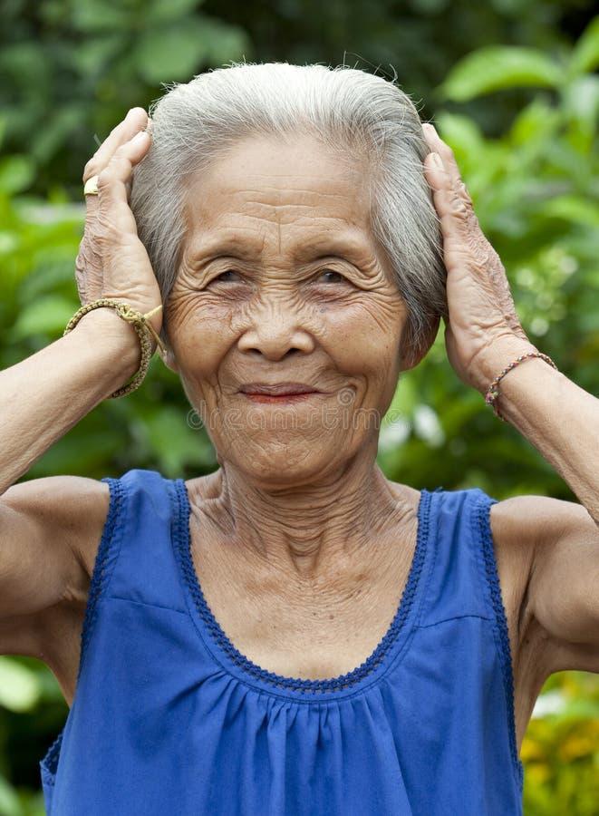 Vieja mujer asiática del retrato con gestos imagen de archivo