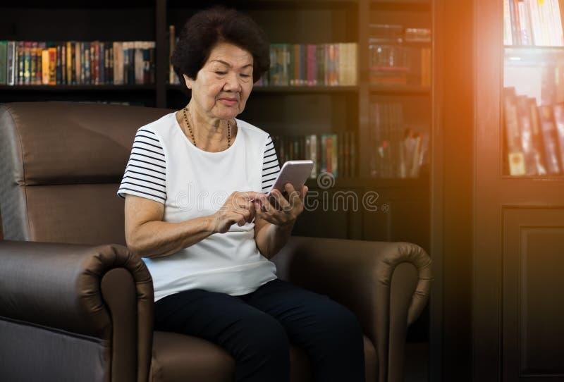 Vieja mujer asiática que usa smartphone fotos de archivo