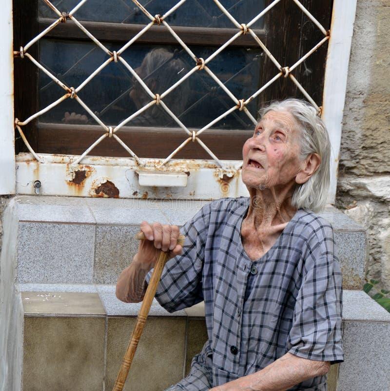 Vieja mujer búlgara pobre con el bastón que camina y usada, vestido lamentable que se sienta en las escaleras en la calle de Varn imagenes de archivo