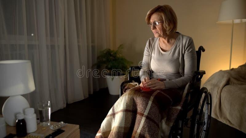 Vieja mujer cansada en los vidrios que llevan de la silla de ruedas que intentan hacer punto, vista pobre imagen de archivo libre de regalías