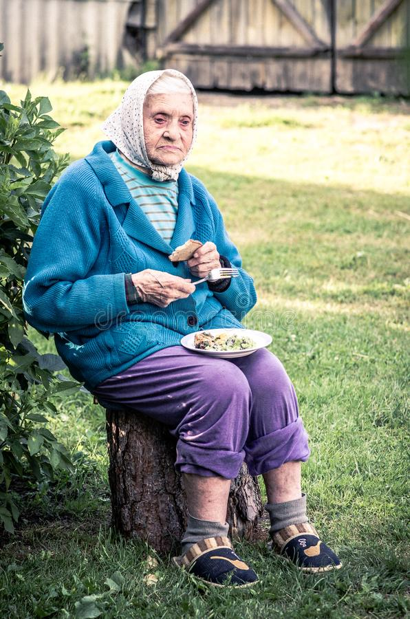 Vieja mujer casual que se sienta al aire libre, comiendo fotografía de archivo libre de regalías