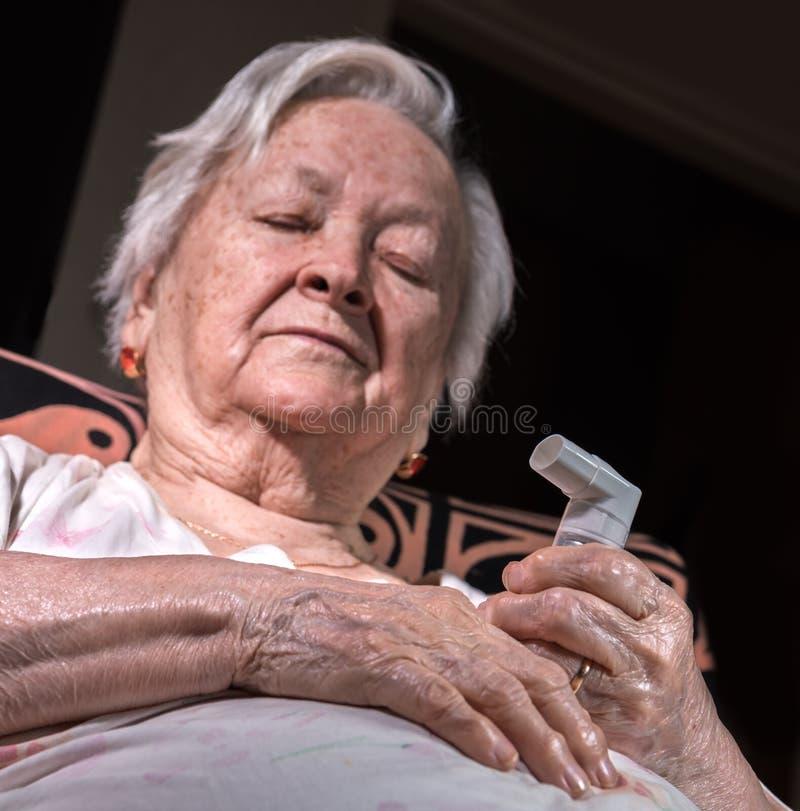 Vieja mujer enferma con el inhalador del asma imagenes de archivo