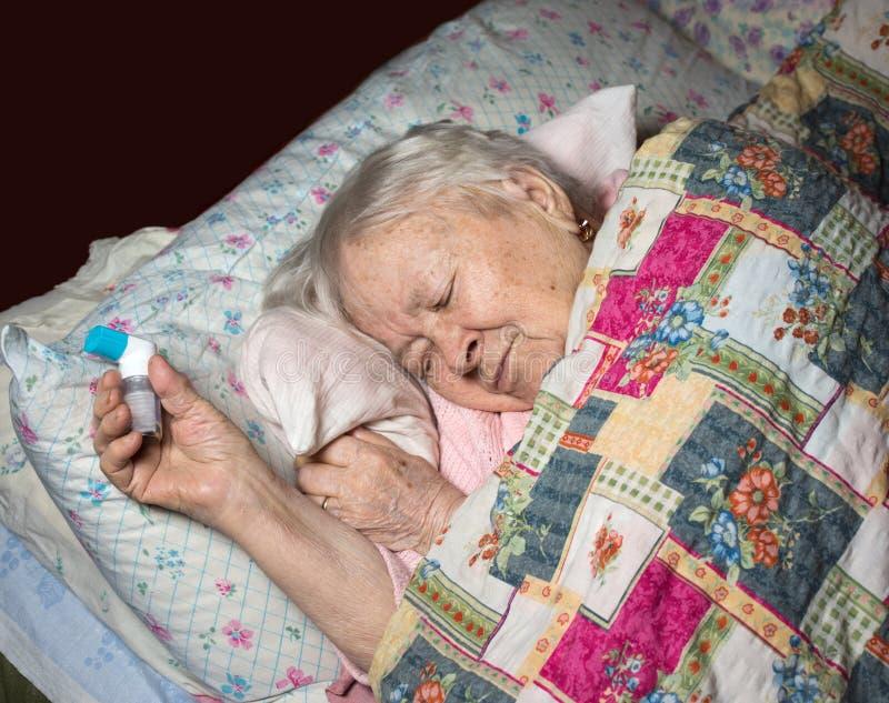 Vieja mujer enferma con el inhalador del asma fotografía de archivo libre de regalías
