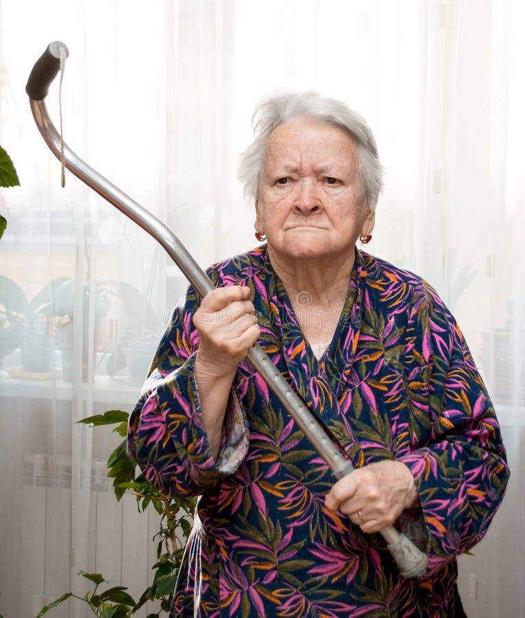 Vieja mujer enojada que amenaza con un bastón imagen de archivo