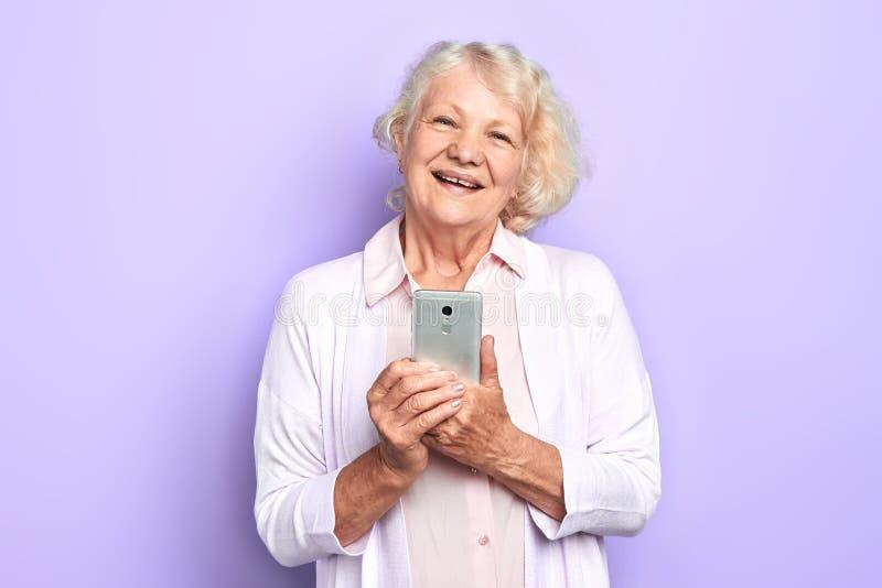 Vieja mujer feliz alegre que usa su smartphone, fondo azul claro aislado fotos de archivo