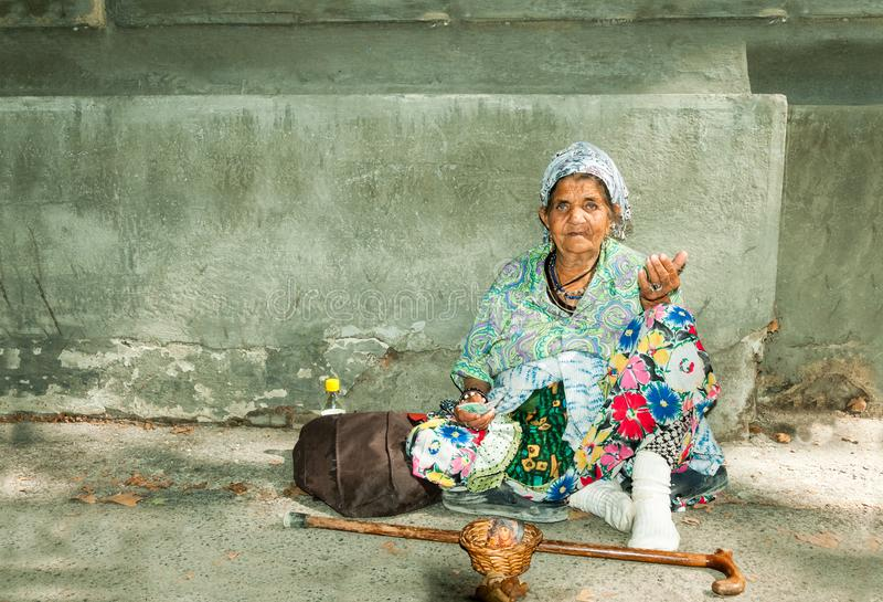 Vieja mujer gitana sin hogar del mendigo con la piel arrugada de la cara que pide dinero en la calle en la ciudad y que mira en l fotografía de archivo libre de regalías