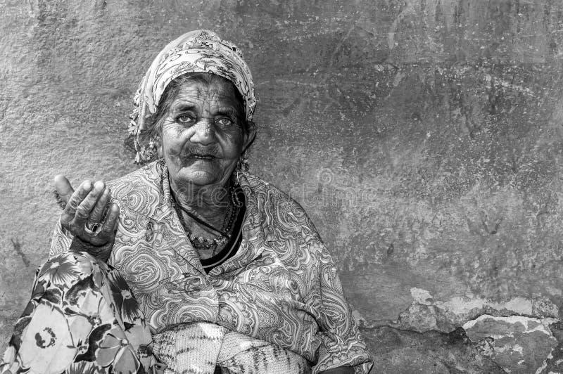 Vieja mujer gitana sin hogar del mendigo con la piel arrugada de la cara que pide dinero en la calle en la ciudad y que mira en l fotos de archivo libres de regalías