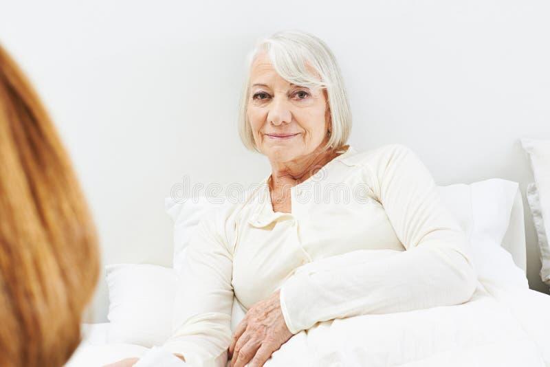 Vieja mujer mayor postrada en cama en clínica de reposo fotografía de archivo