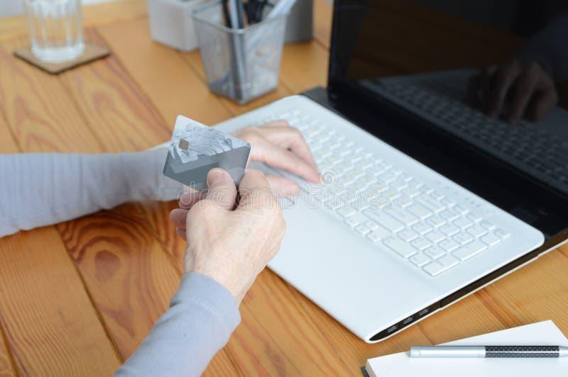 Vieja mujer mayor que usa el ordenador portátil y sosteniendo la tarjeta de crédito imágenes de archivo libres de regalías