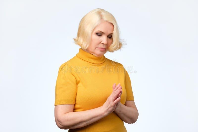 Vieja mujer mayor triste en la ropa amarilla que mira abajo imágenes de archivo libres de regalías