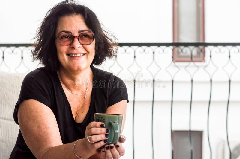 Vieja mujer morena feliz que sostiene una taza de café en sus manos imagenes de archivo