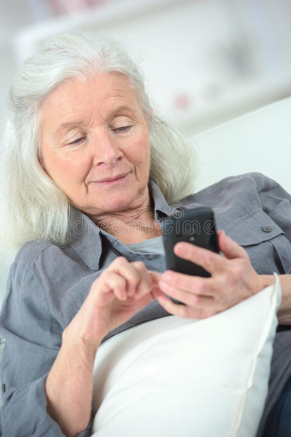 Vieja mujer sonriente con el teléfono móvil imagenes de archivo
