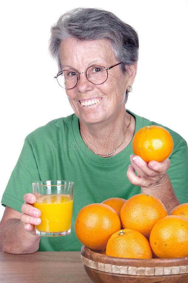 Vieja mujer sonriente con el zumo de naranja fotos de archivo libres de regalías