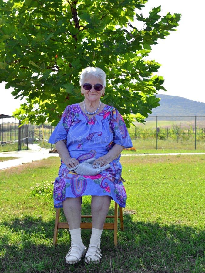 Vieja mujer sonriente en los sungalsses que se sientan en una silla imagen de archivo libre de regalías