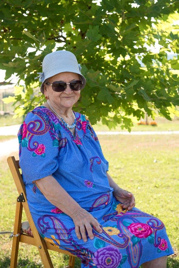 Vieja mujer sonriente en los sungalsses que se sientan en una silla imagenes de archivo