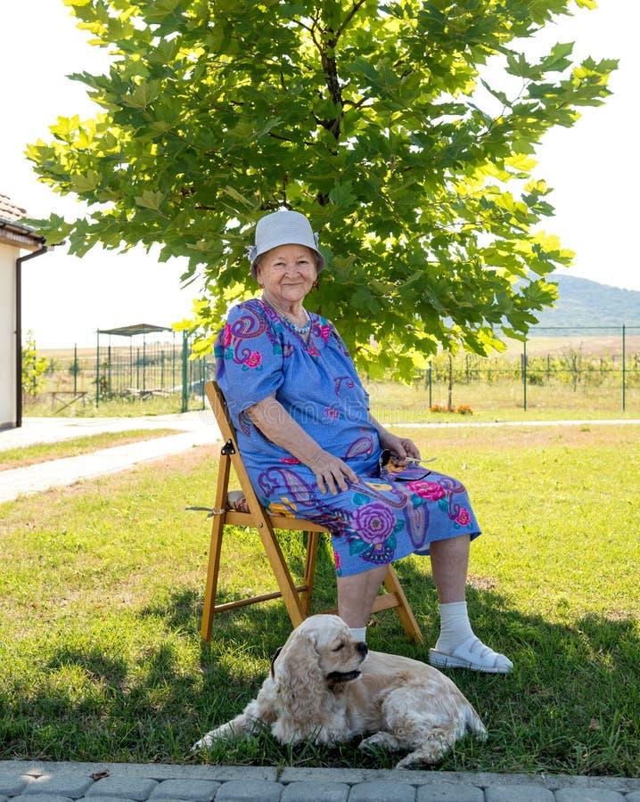Vieja mujer sonriente que se sienta en la silla con el perro fotografía de archivo