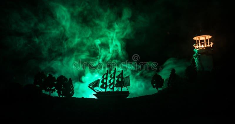 Vieja navegación de madera del buque de guerra por noche cerca del faro o faro y velero Fondo de niebla oscuro Foco selectivo imágenes de archivo libres de regalías